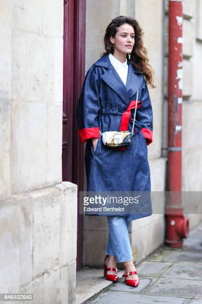 A guest wears a white top a blue and red coat blue denim jeans pants and red shoes outside the JOUR/NE show during Paris Fashion Week Womenswear...