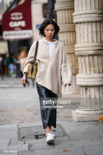Guest wears a white top, a fluffy beige wool oversized cardigan, a camel suede bag, black leather pants, white mesh sneakers, outside Unravel...