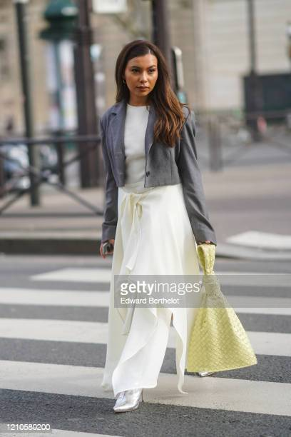 Guest wears a white top, a gray jacket, white skirt, a pale yellow woven bag, silver pointy boots, outside Miu Miu, during Paris Fashion Week -...