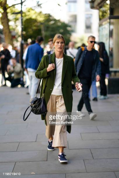 A guest wears a white top a green long coat beige flare pants sneakers a black leather bag during London Fashion Week September 2019 on September 13...