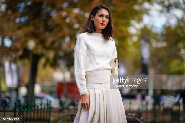 A guest wears a white top a pleated skirt outside Chanel during Paris Fashion Week Womenswear Spring/Summer 2018 on October 3 2017 in Paris France