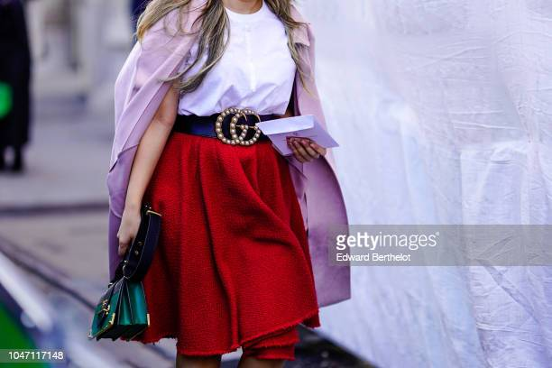 A guest wears a white top a red skirt a Gucci belt a pink jacket a Prada green bag outside Valentin Yudashkin during Paris Fashion Week Womenswear...