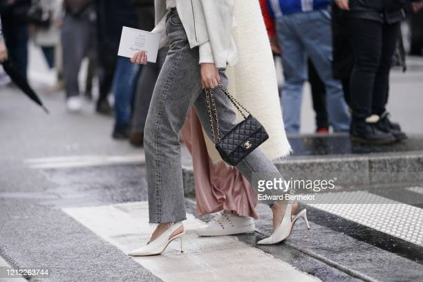Guest wears a white top, a white leather biker jacket, grey snow-wash ripped hem jeans, white pointy heeled slingback pumps, a black Chanel bag,...
