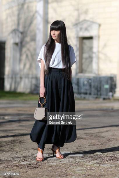 Guest wears a white top, and a black skirt, outside the Chloe show, during Paris Fashion Week Womenswear Fall/Winter 2017/2018, on March 2, 2017 in...