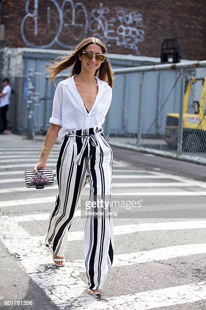 A guest wears a white top and black and white striped trousers at the Zimmermann show at Metropolitan West on September 9 2016 in New York City