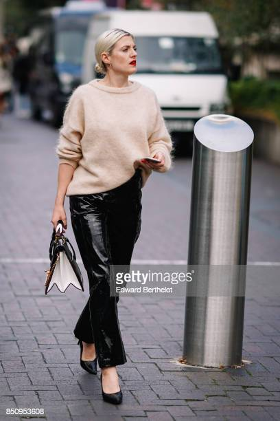 A guest wears a white top black pvc flare pants a bag black shoes outside Roland Mouret during London Fashion Week September 2017 on September 17...
