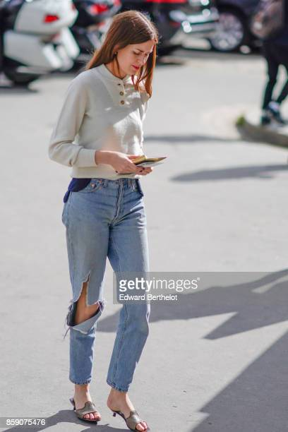 A guest wears a white top blue ripped jeans outside Elie Saab during Paris Fashion Week Womenswear Spring/Summer 2018 on September 30 2017 in Paris...