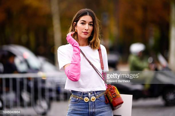 A guest wears a white top pink sleeves blue jeans an orange Chanel bag outside Chanel during Paris Fashion Week Womenswear Spring/Summer 2019 on...