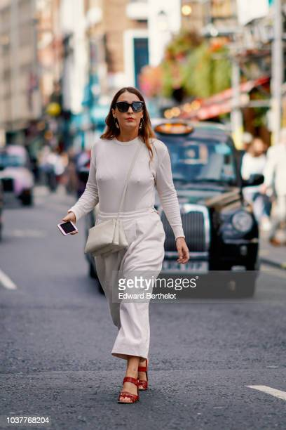 A guest wears a white top white pants red shoes a white bag during London Fashion Week September 2018 on September 15 2018 in London England