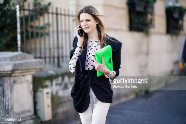 A guest wears a white top with ablack design a black gathered jacket white corduroy pants a neon green Prada bag outside Dries Van Noten during Paris...