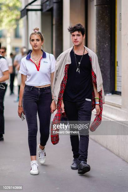A guest wears a white top with blue and red collar black jeans a guest wears a long necklace a beige jacket with a red tartan inner lining outside...