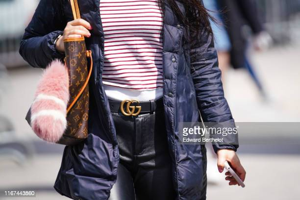 A guest wears a white top with thin red stripes a navy blue padded jacket a Gucci belt black leather pants a Louis Vuitton monogram bag outside the...