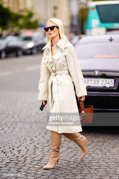 A guest wears a white trench coat and a brown bag outside Chanel during Paris Fashion Week Womenswear Spring/Summer 2019 on October 2 2018 in Paris...