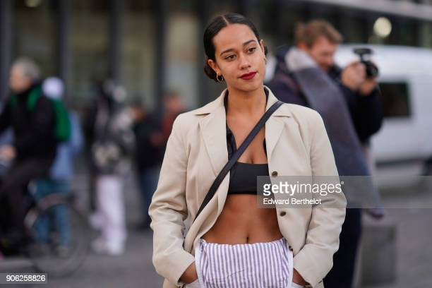 A guest wears a white trench coat black bras striped pants black sneakers outside Off White during Paris Fashion Week Menswear Fall Winter 20182019...
