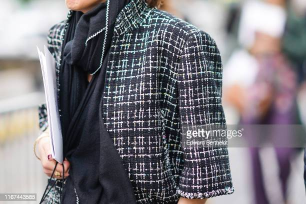 A guest wears a white trimmed black scarf a high collar black and white jacket outside the Chanel Cruise Collection 2020 At Grand Palais on May 03...