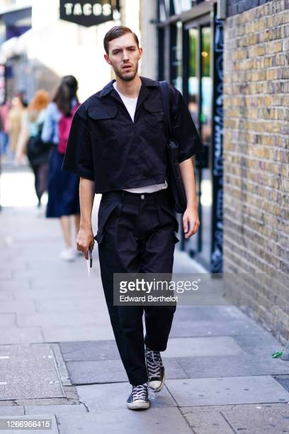 Guest wears a white t-shirt, a black shirt with pockets, black pants, sneakers, during London Fashion Week September 2019 on September 14, 2019 in...