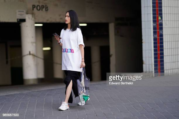 A guest wears a white tshirt a black skirt white sneakers a transparent bag outside 1017 ALYX 9SM during Paris Fashion Week Menswear SpringSummer...