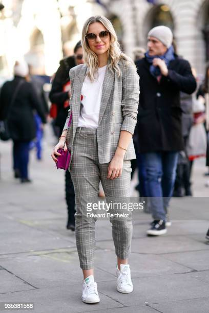 A guest wears a white tshirt a checked gray blazer and suit pants white sneakers a purple bag during London Fashion Week February 2018 on February 16...
