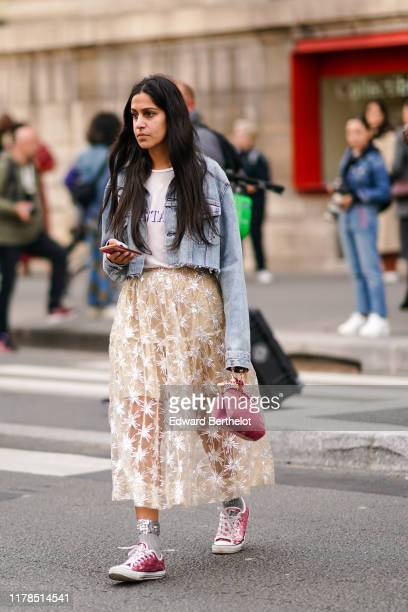 Guest wears a white t-shirt, a light-blue washed-out denim jacket with a cut hem, a gathered and ruffled see-through embroidered tulle flowing skirt,...