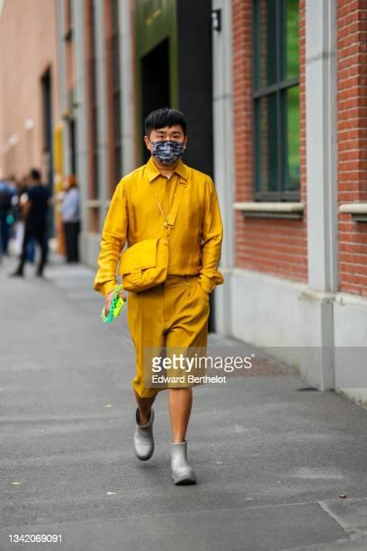 Guest wears a white t-shirt, a yellow mustard Fendi shirt, matching yellow mustard Fendi shorts, a yellow nylon Fendi crossbody bag, gray shiny...