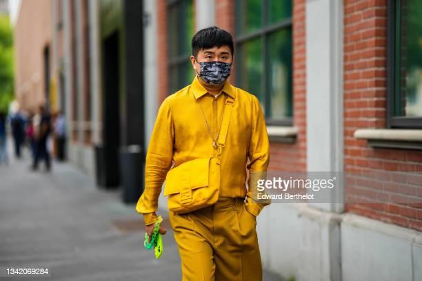 Guest wears a white t-shirt, a yellow mustard Fendi shirt, matching yellow mustard Fendi shorts, a yellow nylon Fendi crossbody bag, outside the...