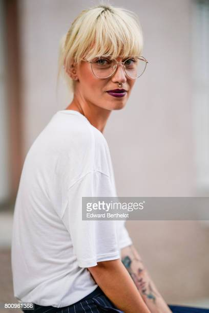 A guest wears a white tshirt glasses outside the Kenzo show during Paris Fashion Week Menswear Spring/Summer 2018 on June 25 2017 in Paris France