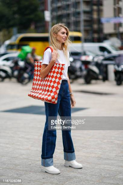 Guest wears a white t-shirt, navy blue denim rolled-up hem pants, white shoes, a large red and white checks woven leather handbag, outside the...