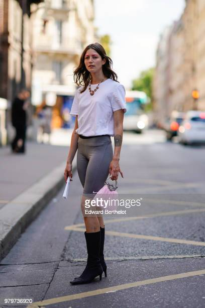 A guest wears a white tshirt Nike gray leggings shorts black high boots a pink bag a necklace outside Y/Project during Paris Fashion Week Menswear...
