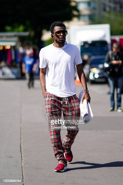 A guest wears a white tshirt red and brown tartan checked pants red shoes outside OffWhite during Paris Fashion Week Menswear SpringSummer 2019 on...