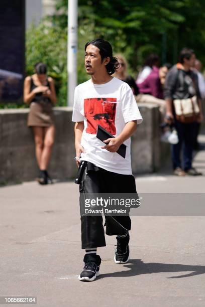 A guest wears a white tshirt with a red patch black cropped large pants black sneakers shoes outside Rick Owens during Paris Fashion Week Menswear...