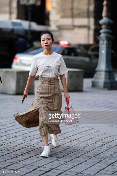Guest wears a white t-shirt with black inscriptions, a light brown checkered flowing skirt, a Louis Vuitton pink bag, white sneakers, outside Louis...