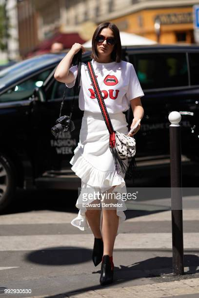 A guest wears a white tshirt with printed love you a white ruffled skirt black shoes a shoulder strap white tiger print bag outside Alexis Mabille...