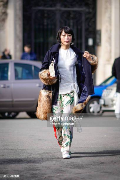 A guest wears a white tunic with a tie on one side exotic print pants a navy blue coat with faux fur lined sleeves a faux fur tote bag a white bag...