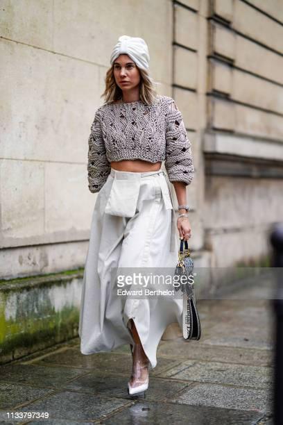 A guest wears a white turban a taupe crop sweater a beige skirt a Dior monogram bag a seethrough vinyl boots outside Nobi Talai during Paris Fashion...