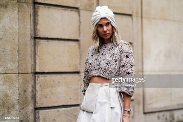A guest wears a white turban a taupe crop sweater a beige skirt outside Nobi Talai during Paris Fashion Week Womenswear Fall/Winter 2019/2020 on...