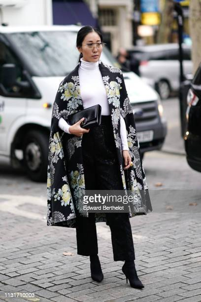 A guest wears a white turtleneck a black brocade cape black pants black shoes a Christian Dior black pouch during London Fashion Week February 2019...