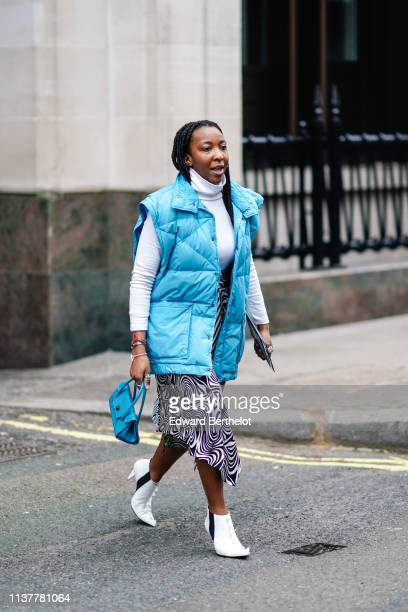 A guest wears a white turtleneck a blue oversize puffer sleeveless vest a blue handbag an asymmetrical skirt white ankle boots during London Fashion...
