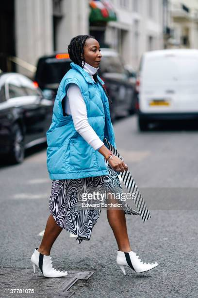 A guest wears a white turtleneck a blue oversize puffer sleeveless vest an asymmetrical skirt white ankle boots during London Fashion Week February...