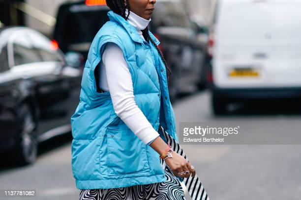 A guest wears a white turtleneck a blue oversize puffer sleeveless vest during London Fashion Week February 2019 on February 16 2019 in London England