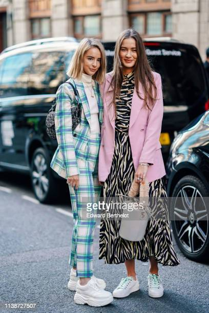 Guest wears a white turtleneck, a white, blue and green checkered jacket, matching pants, a Dior monogram saddle bag, white platform sneakers ; A...