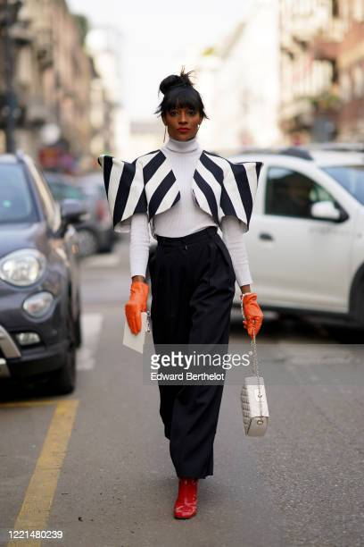 A guest wears a white turtleneck pullover a black and white striped jacket with large shoulder pads balck pants a white quilted bag red shiny boots...