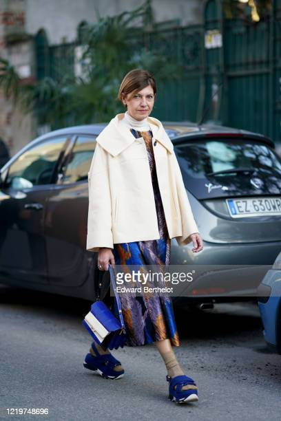 Guest wears a white turtleneck pullover, a white jacket, a blue and purple lustrous dress, a blue and white leather bag, brown socks, blue shoes,...