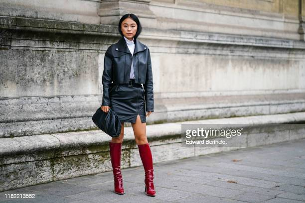 Guest wears a white turtleneck top, a black leather jacket, black leather skirt, a belt, a puff bag, red shiny high boots, outside Unravel Project,...
