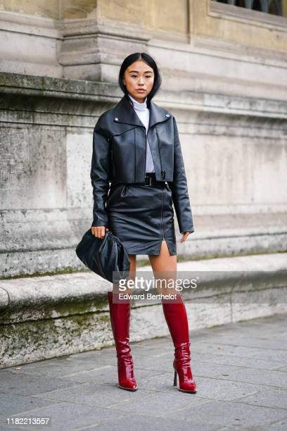 A guest wears a white turtleneck top a black leather jacket black leather skirt a belt a puff bag red shiny high boots outside Unravel Project during...