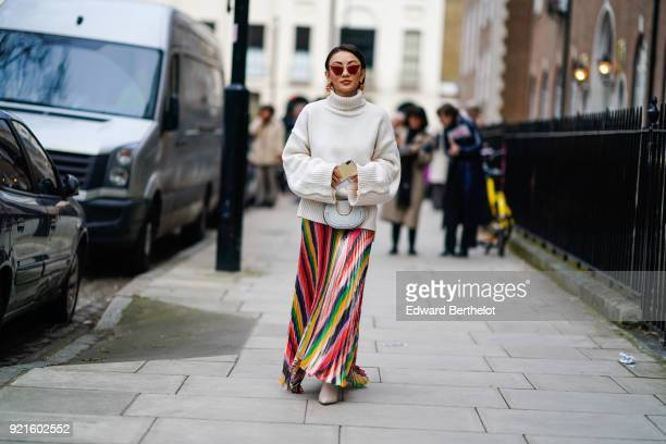 A guest wears a white turtleneck top a colored striped skirt sunglasses during London Fashion Week February 2018 on February 18 2018 in London England