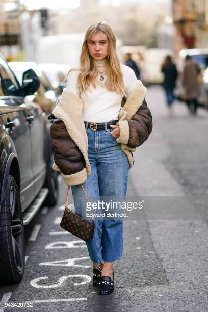 A guest wears a white turtleneck top a necklace an aviator jacket a Gucci belt a Vuitton bag blue jeans black shoes during London Fashion Week...