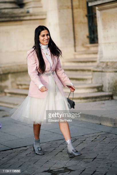 Guest wears a white turtleneck with red hearts print at the top, a pink jacket, a flowing white tulle skirt, a shiny black bag, glittering grey...