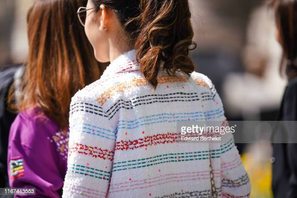 A guest wears a white tweed coat with colorful thin stripes outside the Chanel Cruise Collection 2020 At Grand Palais on May 03 2019 in Paris France