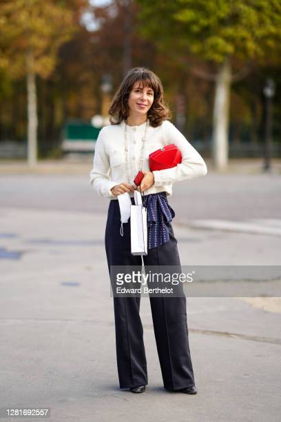 Guest wears a white tweed jacket, a long bejeweled necklace, a red bag, black flared pants, outside Chanel, during Paris Fashion Week - Womenswear...