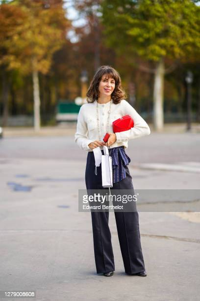 Guest wears a white tweed jacket, a red bag, a necklace, flared pants, leather shoes, outside Chanel, during Paris Fashion Week - Womenswear Spring...